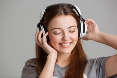 Smiling lovely young woman listening to music using headphones