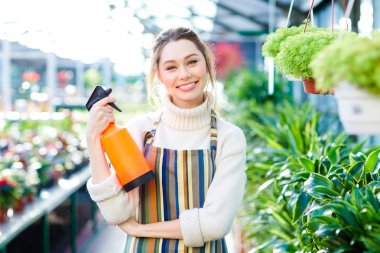 Cheerful attractive woman gardener standing in orangery with water pulverizer