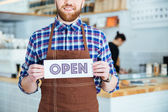 Fotografie Smiling bearded waiter in brown apron showing open sign