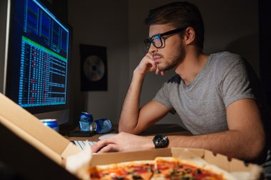 Pensive young developer in glasses coding at home