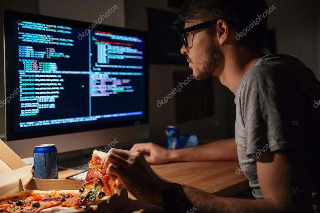 Konzentrierter Softwareentwickler Pizza Essen und Codierung ...