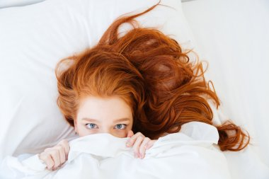 Scared woman lying in bed and hiding under the sheet