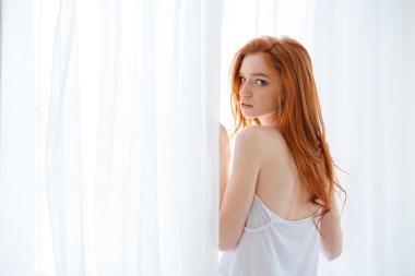 Tender woman standing near the window