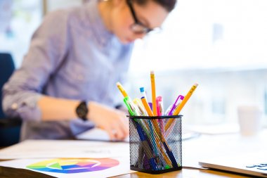 Serious female fashion designer making sketches in office