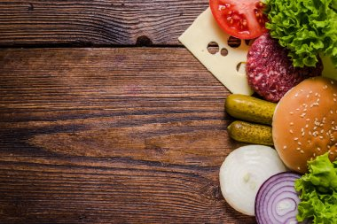 Ingredients for hamburgers on wooden table, border background