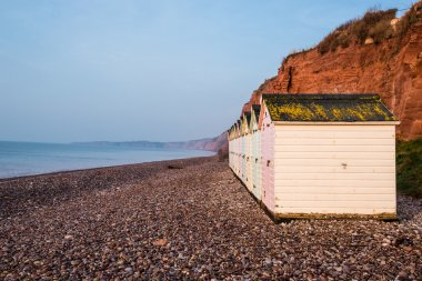 Beach hut row in pastel colors, red rock cliff background