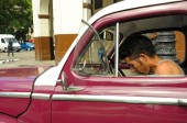 Havanna, Kuba - május 30., 2013 a fiatal kubai férfi ül a régi klasszikus amerikai autó-Havanna, Kuba. Kuba ismert a szépség, a veterán autók