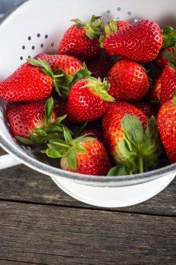 Sweet ripe strawberries in rustic colander