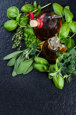 Fresh herbs with olive oil on black background