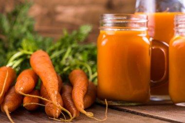 Carrot juice in mason jar on wooden background