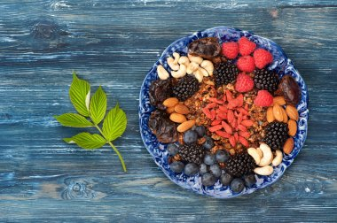 Ingredients healthy food - berries, nuts, granola, goji berries, figs. Top view, horizontal