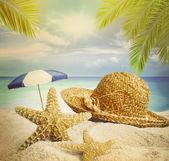 Sandy beach, slaměný klobouk a hvězdice v létě