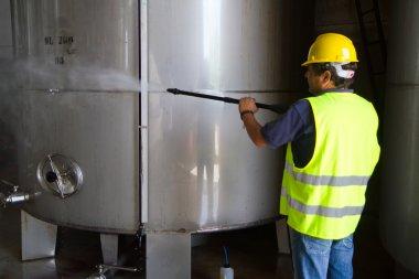 Worker in hard hat pressure washing