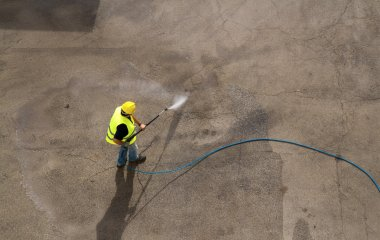 Worker in hard hat pressure washing