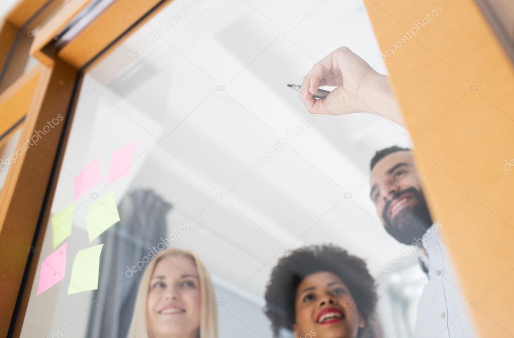 Joyeuse équipe créative écriture sur verre blanc bureau