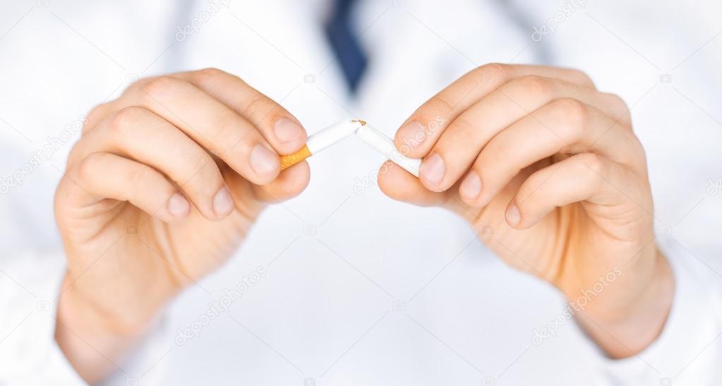 homme brisant la cigarette avec les mains photographie syda productions 71592387. Black Bedroom Furniture Sets. Home Design Ideas