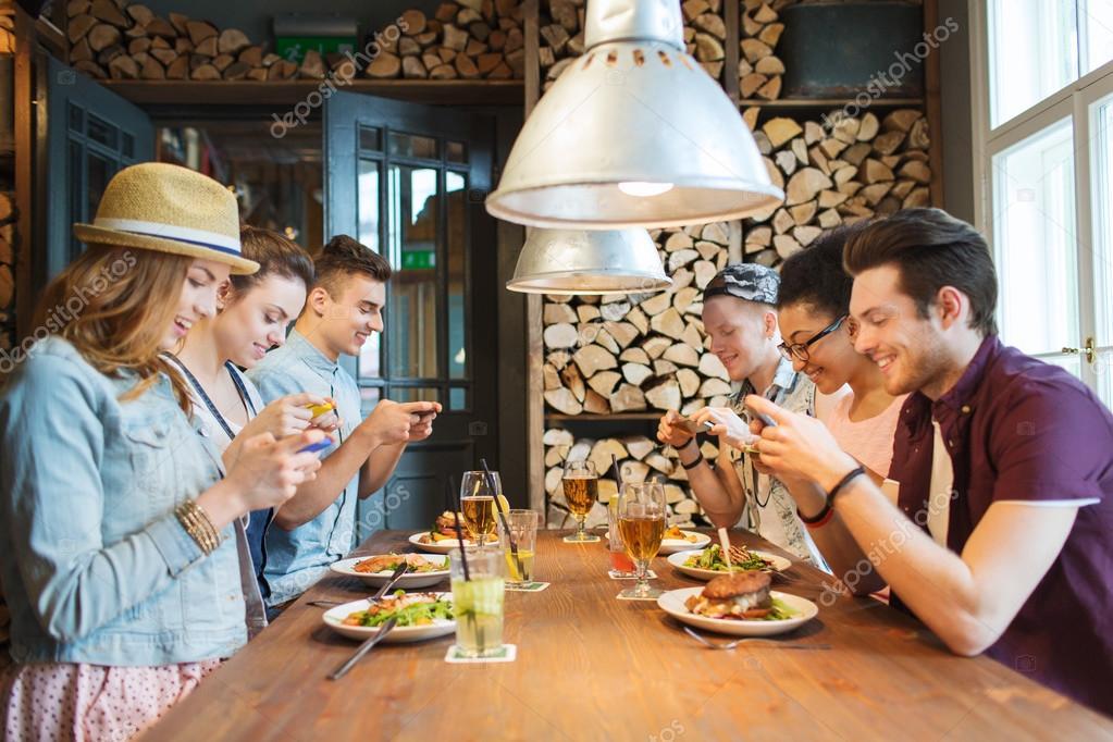 Freunde Mit Smartphone Essend Am Restaurant Stockbild