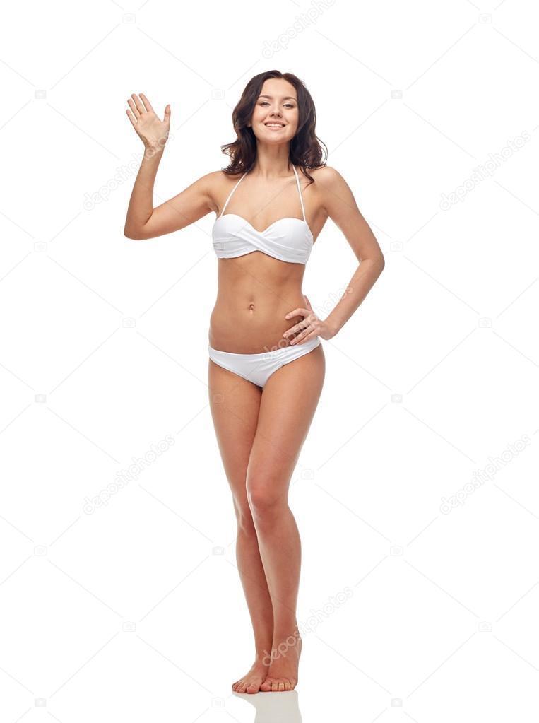 1b4a60d4ff33c4 Ludzie, moda, strój kąpielowy, lato i koncepcja - szczęśliwa młoda kobieta  w białym bikini kostium kąpielowy macha ręką — Zdjęcie od Syda_Productions