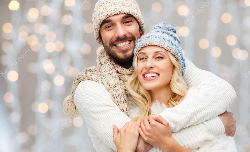 Счастливая пара в зимней одежде, обниматься над огнями — стоковое фото