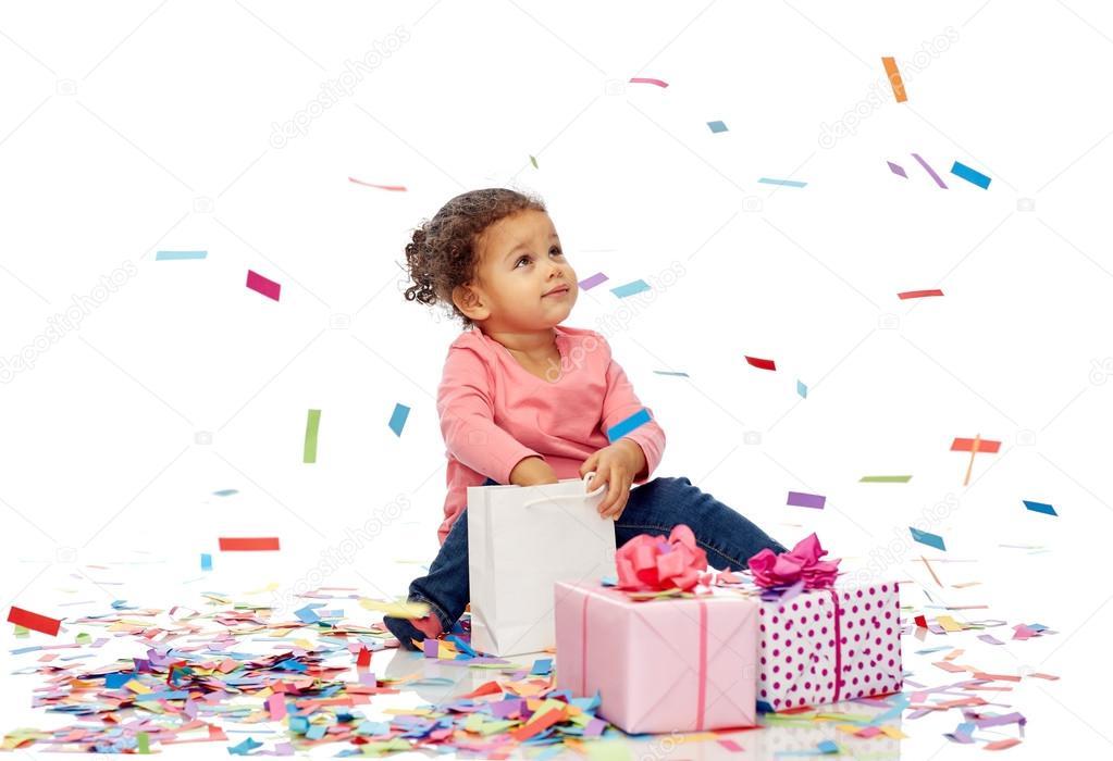 b93870f9d0b Παιδική ηλικία, γενέθλια, κόμμα, διακοπές και άνθρωποι έννοια - ευτυχισμένη  κοριτσάκι αφροαμερικάνων μωρό με κουτιά δώρων και κομφετί παίζοντας με  τσάντα ...