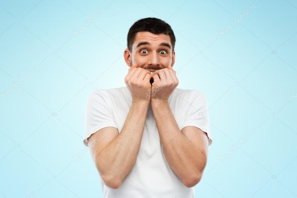 scared man in white t shirt over blue background stock photo