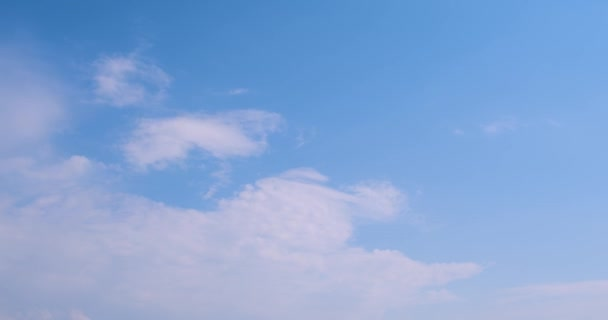 Blue sky in horizon with soft white sunny clouds time lapse, summer beautiful happy day, fluffy, puffy mass fast moving. Filmed on cinema camera