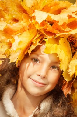 Girl with yellow autumn leaves on her head
