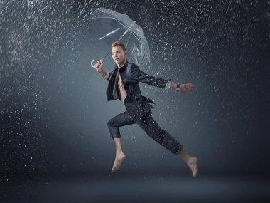 Handsome man jumping and dancing in the rain
