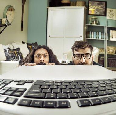 Two funny computer scientits staring at a keybord