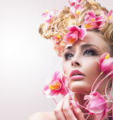 Krásy dívka modelu s krásnými květinami ve vlasech