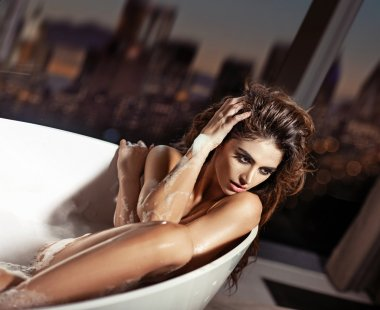Beautiful young woman taking a bath in the bathtub