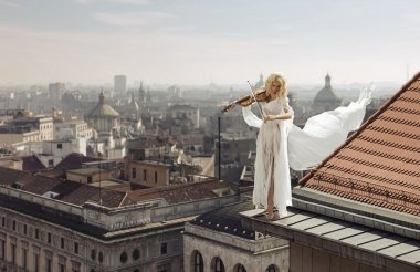 Woman playing the violin on the top of the edge of the roof