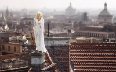 Blonde standing on the chimney with the violin