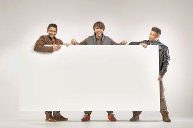 Three cheerful guys holding the board
