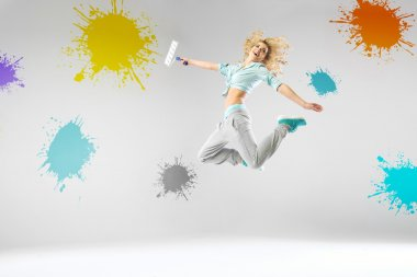 Woman jumping and paiting walls