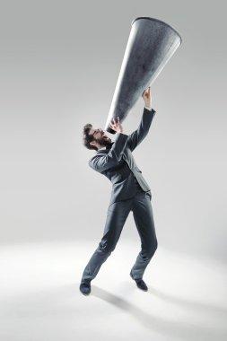 Elegant man yelling over the huge megaphone