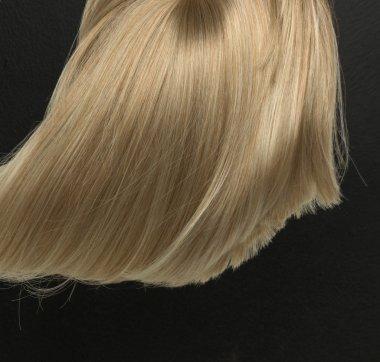 Dense, straight blond wig lying on black background
