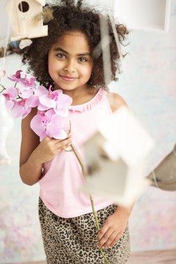 Pretty little girl holding a flower