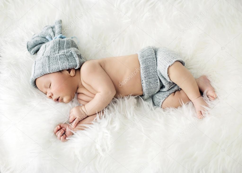 Newborn child sleeping on the blanket