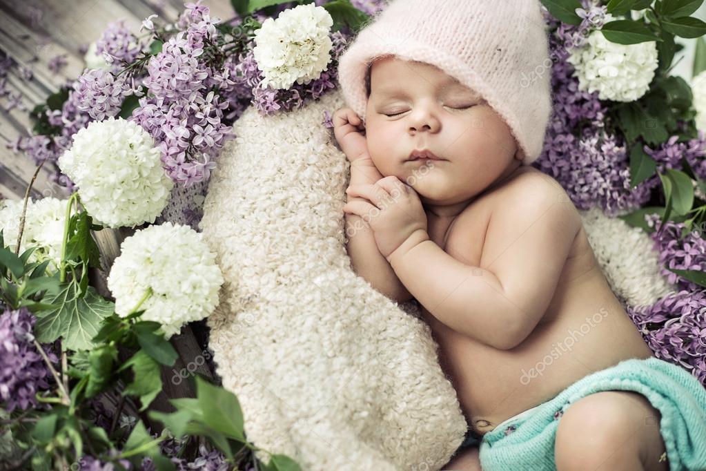 cute boy sleeping among the flowers