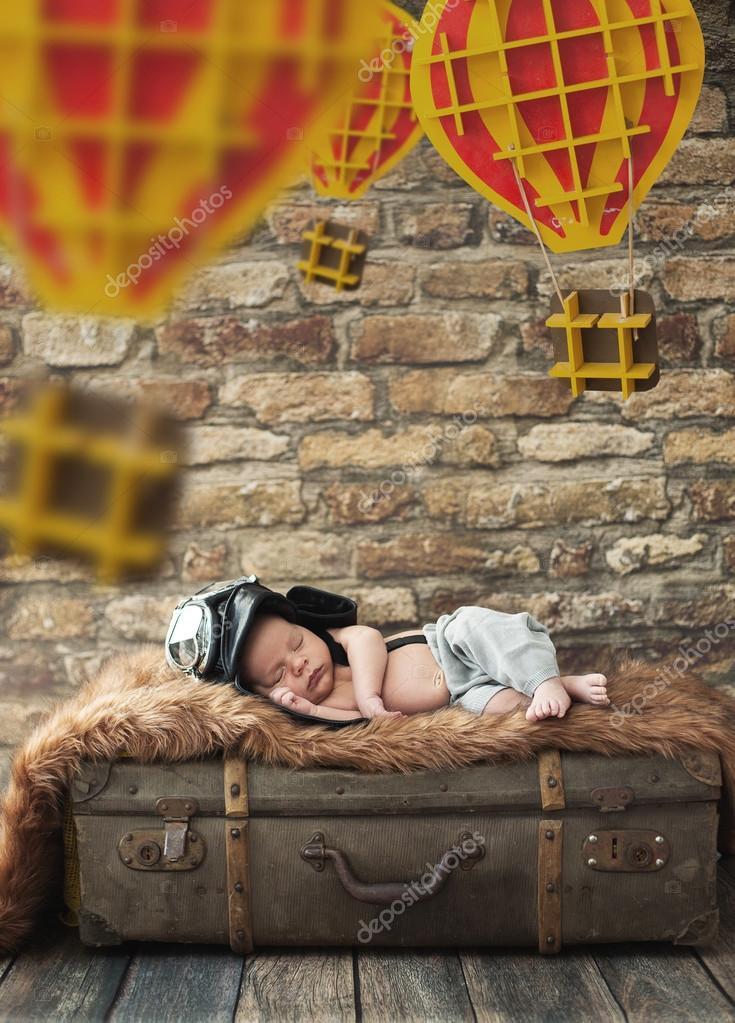 Cute boy sleeping on the luggage