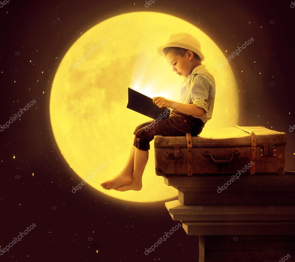 Cute little boy reading a book in the moon light