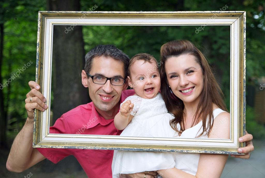Cheerful family posing with the frame