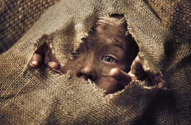 Little homeless boy wearing a bag