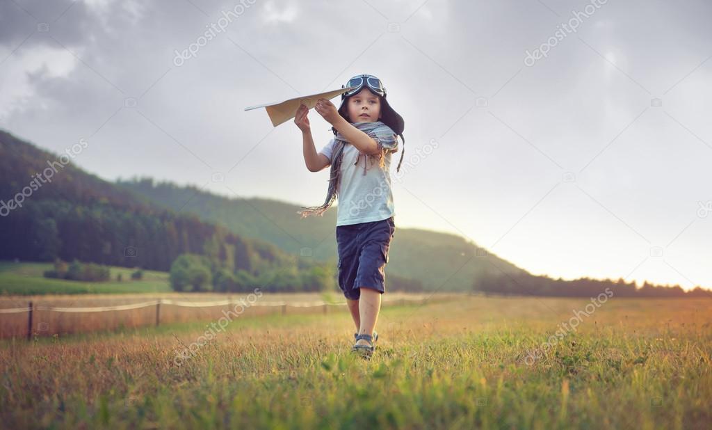 Cute little boy playing toy plane