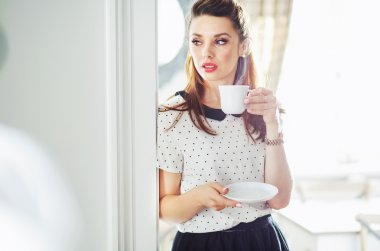 Adorable woman drinking tasty coffee