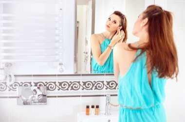 Pretty woman doing a make-up in the bathroom