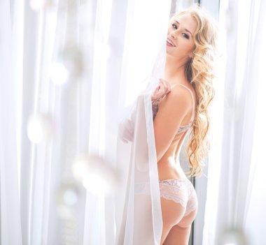 Portrait of a blond sensual woman in bedroom