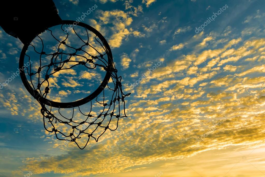 Silhouette of basketball hoop with dramatic sky
