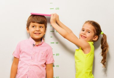 Boy and girl measure height by wall scale